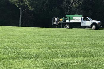 Our fertilizing truck applying fertilizer and weed control on a large lawn in Mayfield, KY..